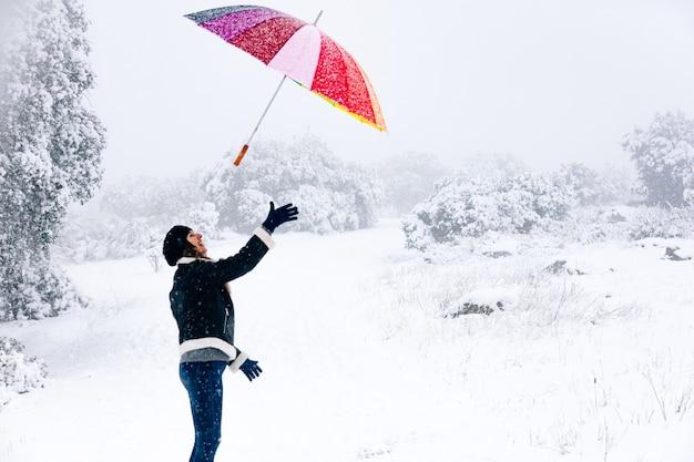 Portrait d'une femme jetant un parapluie coloré en l'air lors d'une chute de neige.