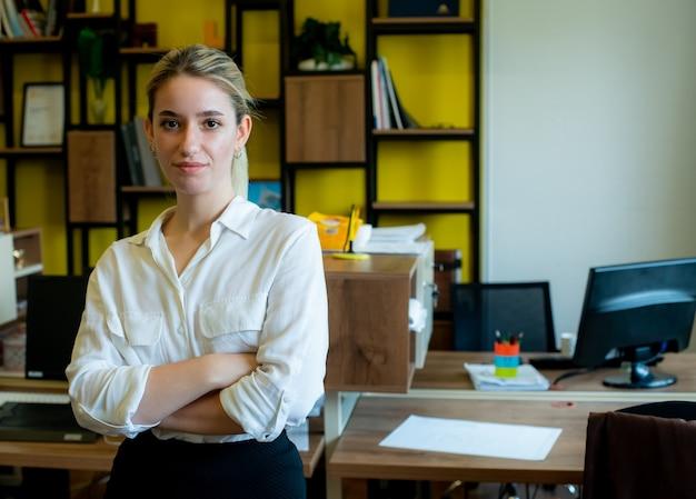 Portrait de femme jeune employé de bureau debout avec les bras croisés regardant la caméra avec une expression de confiance sérieuse sur le visage travaillant au bureau