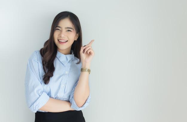 Portrait de femme jeune entreprise asiatique pointant vers le haut sur fond blanc.
