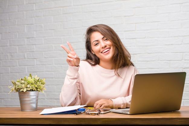 Portrait de femme jeune étudiante latine assise sur son bureau amusant et heureux, positif et naturel, faisant un geste de victoire, concept de paix