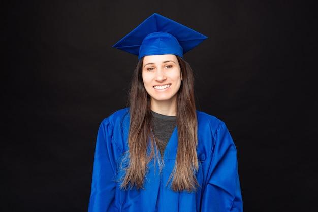 Portrait de femme jeune étudiante souriante portant chapeau et baccalauréat
