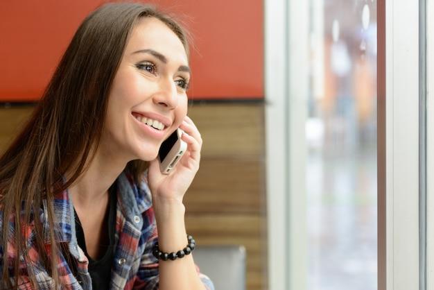 Portrait de femme jeune hipster belle détente au café à l'intérieur