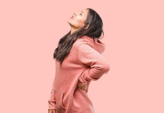 Portrait de femme jeune indienne fitness avec maux de dos en raison de stress au travail, fatigué et astucieux