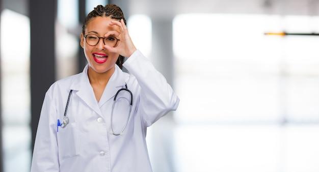 Portrait d'une femme jeune médecin noir gaie et confiante faisant geste ok