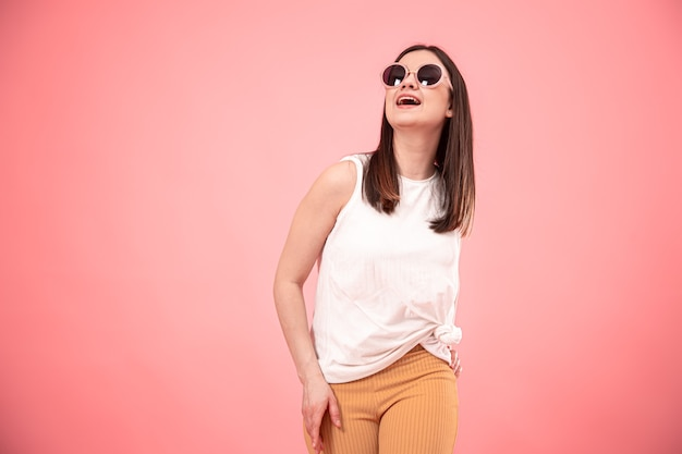 Portrait de femme jeune mode à lunettes de soleil avec sourire sur l'espace de copie isolé visage.
