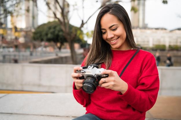 Portrait de femme jeune photographe à l'aide d'un appareil photo numérique professionnel à l'extérieur.
