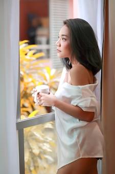 Portrait de femme jeune et sexy se réveiller et voir la vue depuis la fenêtre de la chambre