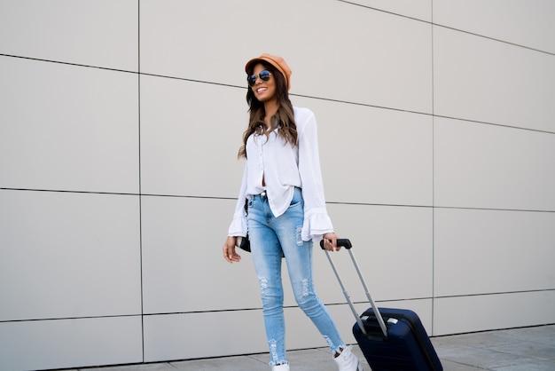 Portrait de femme jeune voyageur portant une valise en marchant à l'extérieur dans la rue. concept de tourisme.