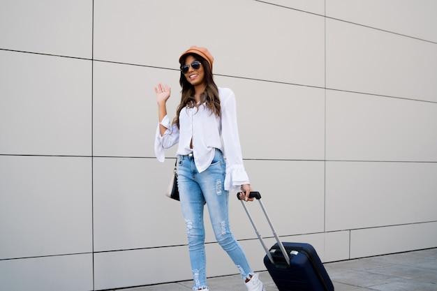 Portrait de femme jeune voyageur portant une valise tout en marchant à l'extérieur dans la rue. concept de tourisme.