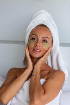 Portrait de femme jolie caucasienne calme avec une serviette sur la tête et les patchs de masque pour les yeux sur le visage concept de soins de la peau du visage femme se détendre sur le lit à la maison