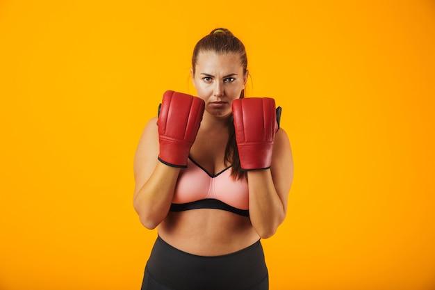 Portrait de femme joufflue sportive en survêtement portant des gants de boxe pratiquant, isolé sur fond jaune
