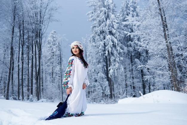 Portrait de femme le jour d'hiver sur fond de paysage enneigé