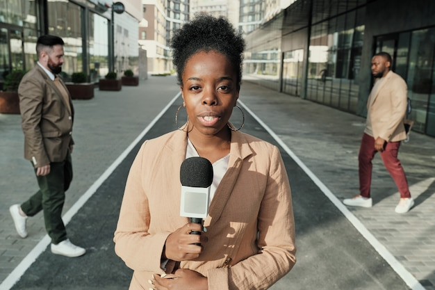 Portrait de femme journaliste africaine parlant au microphone, elle travaille dans la rue à l'extérieur