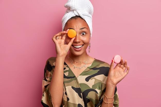 Portrait de femme joyeuse et animée joue avec de délicieux macarons, habillé avec désinvolture, porte une serviette enveloppée sur la tête, aime manger un dessert français, pose contre un mur rose. les gens et la nourriture