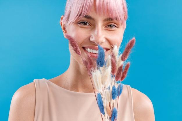 Portrait de femme joyeuse aux cheveux roses souriant à la caméra tenant de l'herbe de la pampa cortaderia séchée