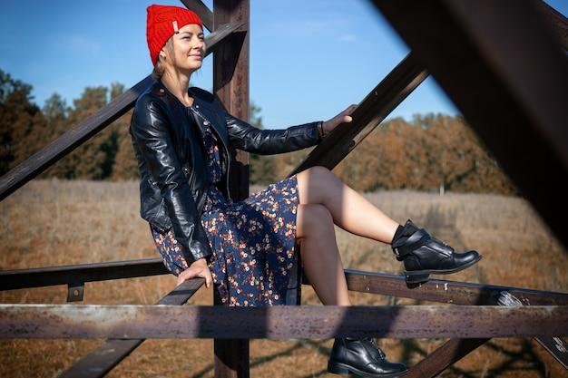 Portrait d'une femme joyeuse avec un bonnet tricoté, un manteau en cuir, une jolie robe et des bottes