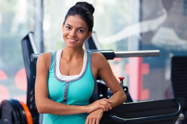 Portrait d'une femme joyeuse debout dans une salle de fitness