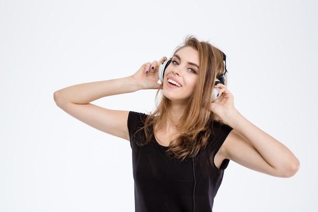 Portrait d'une femme joyeuse écoutant de la musique dans des écouteurs isolés sur fond blanc
