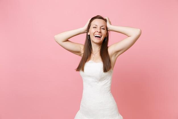 Portrait d'une femme joyeuse et heureuse en belle robe blanche debout, gardant les mains près de la tête