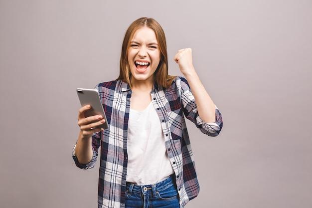 Portrait d'une femme joyeuse heureuse célébrant le succès en se tenant debout et en regardant le téléphone mobile.