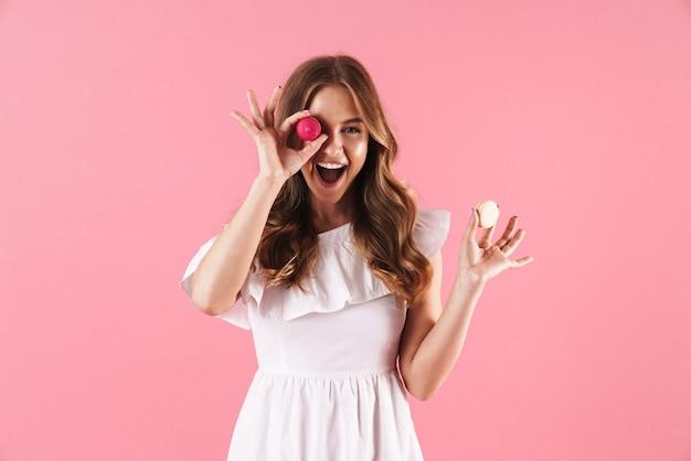 Portrait d'une femme joyeuse et heureuse vêtue d'une robe blanche souriante à la caméra et tenant des biscuits macaron isolés sur un mur rose