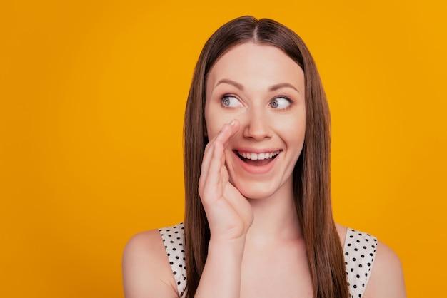 Portrait de femme joyeuse parler paume bouche ouverte regard côté espace vide sur fond jaune