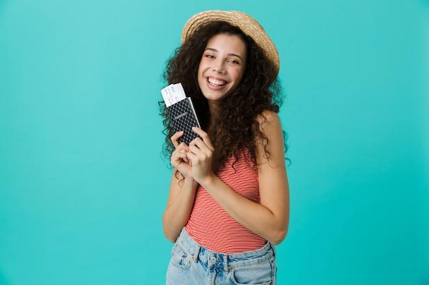 Portrait de femme joyeuse portant un chapeau de paille se réjouissant tout en tenant un passeport et des billets, isolé sur mur bleu