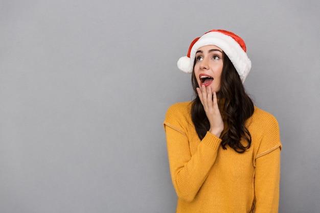 Portrait de femme joyeuse portant le chapeau rouge du père noël se demandant et regardant vers le haut à copyspace, isolé sur fond gris