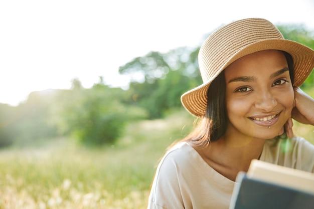 Portrait d'une femme joyeuse portant un piercing aux lèvres et un chapeau de paille, un livre de lecture assis sur l'herbe dans un parc verdoyant