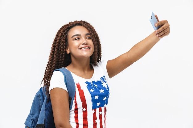 Portrait d'une femme joyeuse portant un sac à dos souriant et prenant une photo de selfie sur son téléphone portable tout en se tenant isolée contre un mur blanc