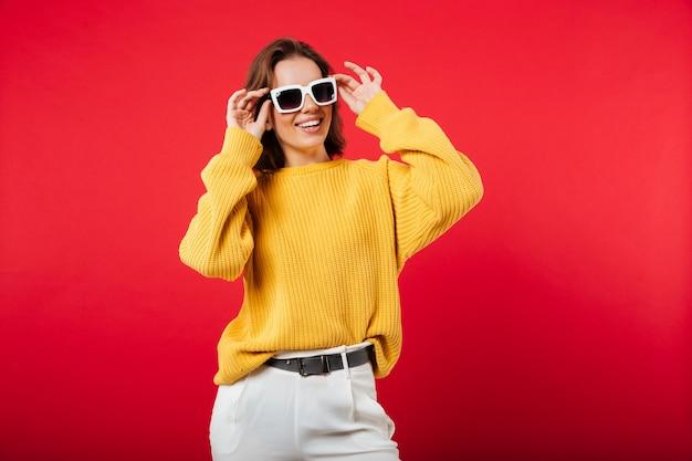Portrait d'une femme joyeuse en posant des lunettes de soleil
