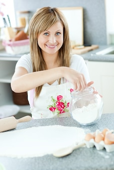 Portrait d'une femme joyeuse préparant un gâteau dans la cuisine
