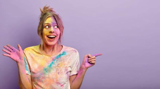 Portrait de femme joyeuse et ravie a le visage sale et des vêtements avec des colorants colorés, célèbre le festival holi en inde, démontre un espace libre sur un mur violet. vacances de couleurs. concept de promotion