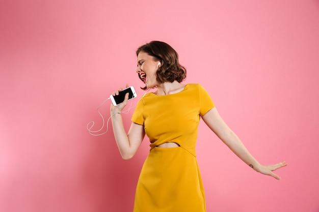 Portrait d'une femme joyeuse en robe et maquillage