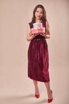 Portrait de femme joyeuse en robe rouge tenant des coffrets cadeaux