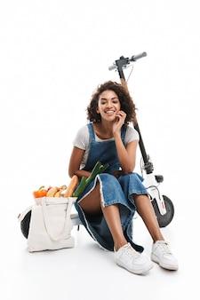 Portrait d'une femme joyeuse souriante assise sur un scooter électronique avec un sac d'épicerie isolé sur un mur blanc