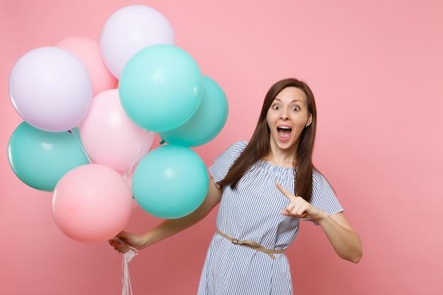 Portrait d'une femme joyeuse surprise avec la bouche ouverte en robe bleue pointant l'index sur des ballons à air colorés isolés sur fond rose. fête d'anniversaire, concept d'émotions sincères.