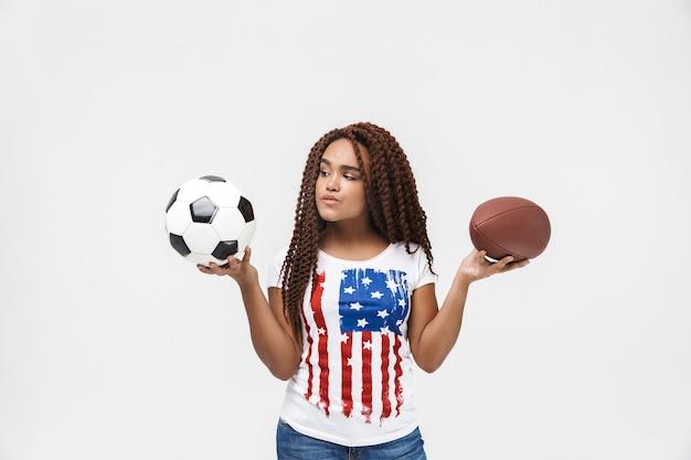 Portrait d'une femme joyeuse tenant des ballons de rugby et de football en se tenant isolé contre un mur blanc
