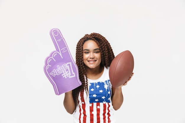 Portrait d'une femme joyeuse tenant un gant de fan numéro un et un ballon de rugby tout en se tenant isolé contre un mur blanc