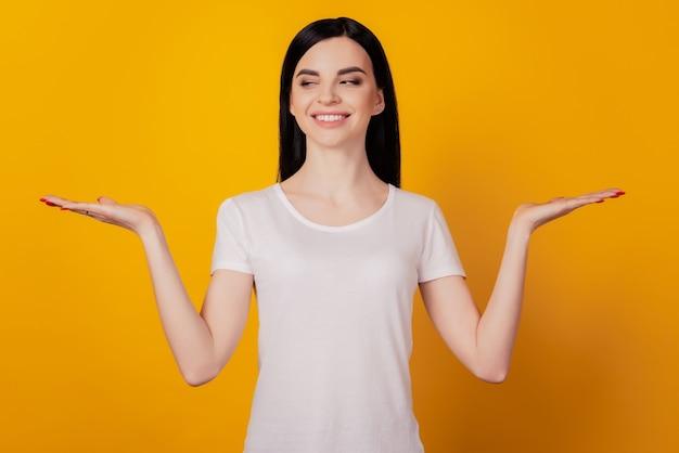 Portrait de femme joyeuse tenir des publicités promo sourire pour contre proposition isolée sur fond jaune