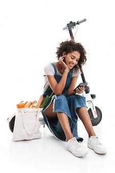 Portrait d'une femme joyeuse utilisant un téléphone portable assis sur un scooter électronique avec un sac d'épicerie isolé sur un mur blanc