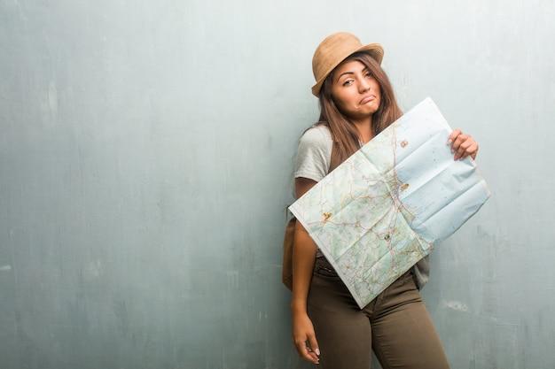 Portrait de femme latine jeune voyageur contre un mur doutant et haussant les épaules