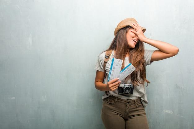 Portrait de femme latine jeune voyageur contre un mur frustrée et désespérée