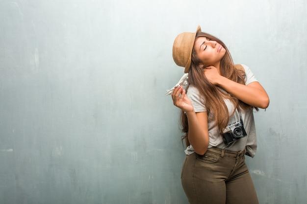 Portrait de femme latine jeune voyageur contre un mur avec maux de dos dus au stress au travail