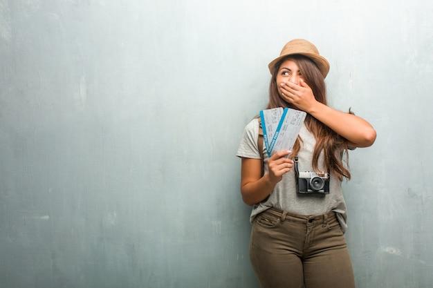 Portrait de femme latine jeune voyageur contre un mur recouvrant sa bouche, symbole du silence et de la répression