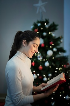 Portrait femme lisant à côté de l'arbre de noël