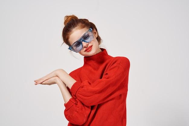 Portrait d'une femme lunettes bleues à la mode posant sur fond clair. photo de haute qualité