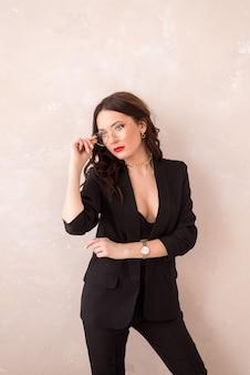 Portrait d'une femme à lunettes sur fond clair. une fille en costume noir tient ses lunettes à la main. belle femme d'affaires avec des lunettes.