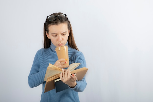 Portrait d'une femme à lunettes lisant un livre avec une tasse de café.