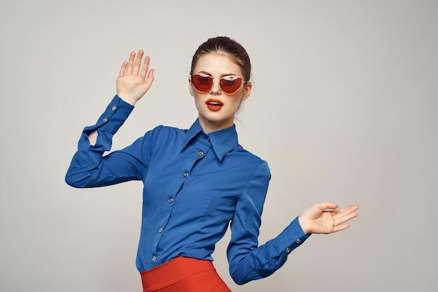 Portrait d'une femme à lunettes de soleil et une chemise bleue sur un fond clair vue recadrée de modèle de copie